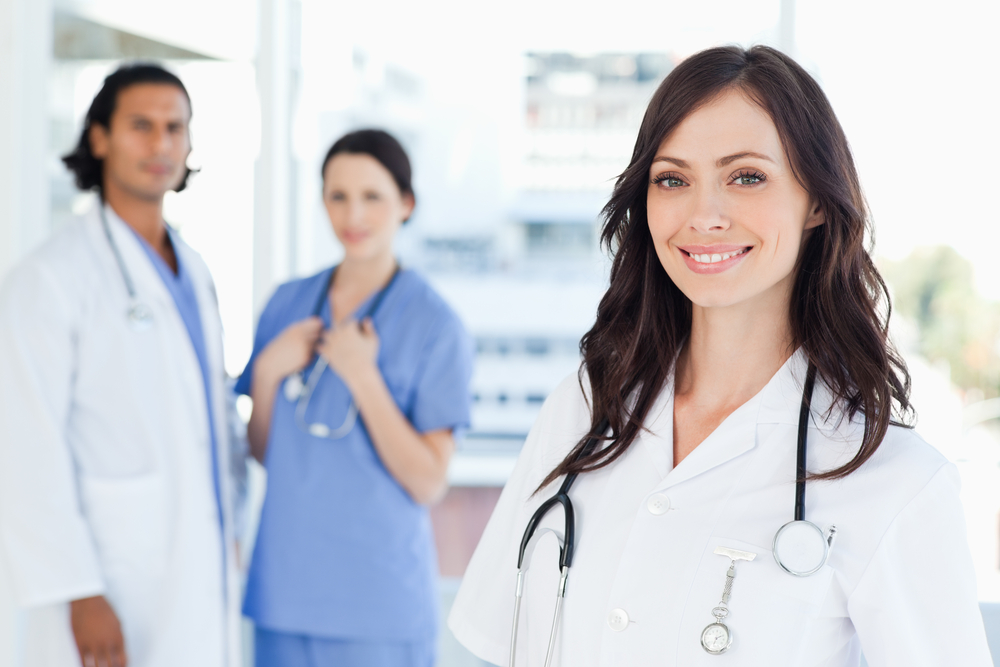 Smiling nurse standing in front of two co-workers